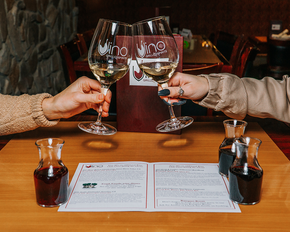 Two people clinking Vino Grille & Spiriys wine glasses with white wine.